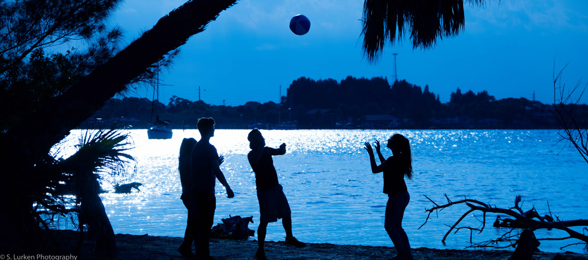 Students Playing Volleyball by the Water